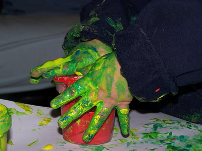 person in black jacket holding red plastic container with paint on hand