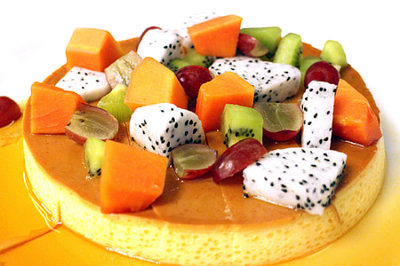 sliced kiwi, papaya, grape, and dragon fruit topped caramel flan