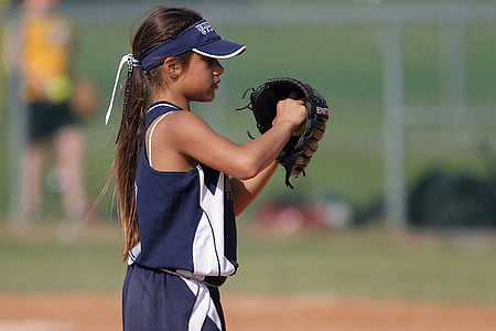 girl playing baseball on field