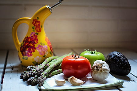 vegetables and spices and yellow floral bottle on surface