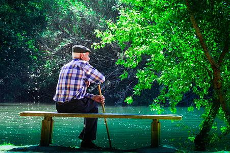 man sitting on bench facing body of water