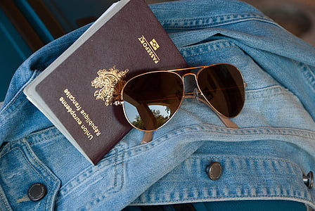 gold framed aviator-style sunglasses and passport