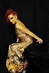 woman wearing gold long-sleeved dress with black background