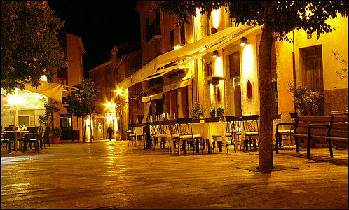 empty tables and chairs near tree during night time