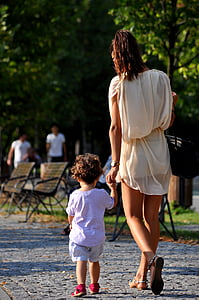 woman wearing white dress holding hand of toddler