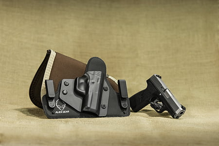 closeup photo of black and gray semi-automatic pistol beside brown and black leather and plastic holster placed on beige textile