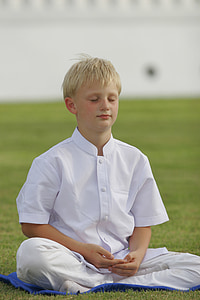 boy wearing white outfit while meditating on green grass field