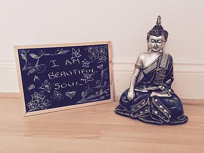 silver-colored Gautama Buddha figurine and black board