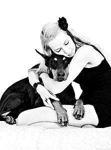 woman hugging adult Doberman pinscher