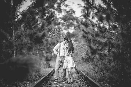 grayscale photography of man and woman standing on train rails
