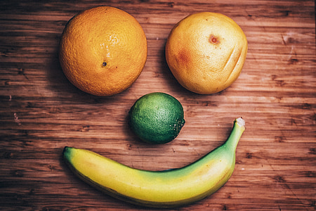two oranges, one lemon, and banana forming a smile on brown wooden surface