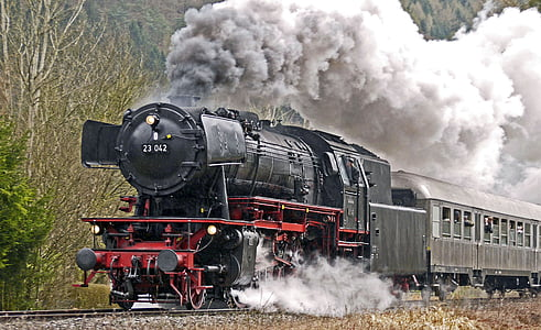 moving black locomotive train covered with thick smoke