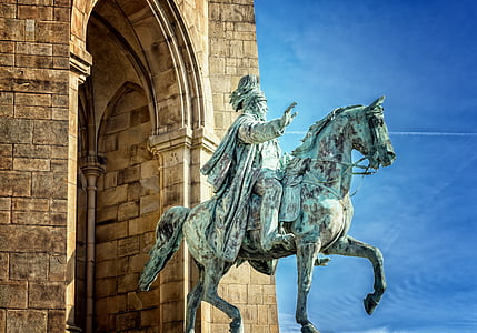 man riding on a horse statue during daytime
