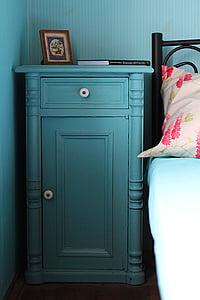 blue wooden cabinet beside black bed