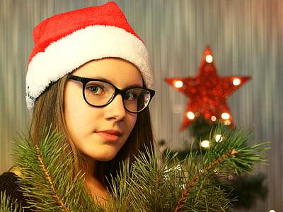 woman wearing Santa hat standing near red star finial