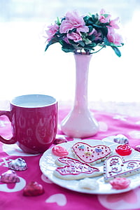 pink petaled flowers with white ceramic vase beside red ceramic mug