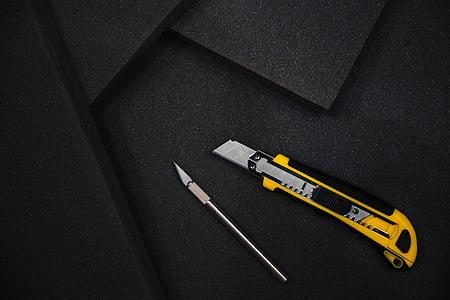 yellow utility knife on black mat