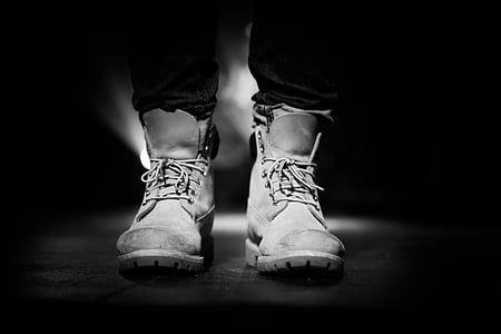 grayscale photography of person wearing pair of boots