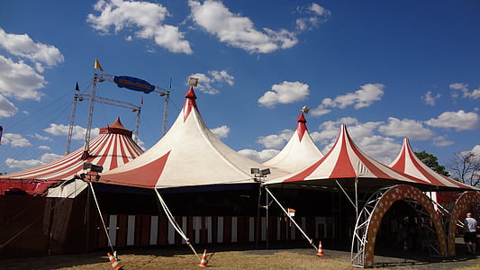 white and red carnival tents under cloudy sky during daytime