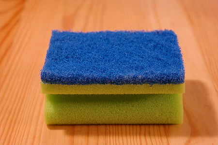 blue and yellow sponge on brown wooden surface