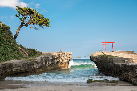 torii arch on top of cliff under clear skies during daytime