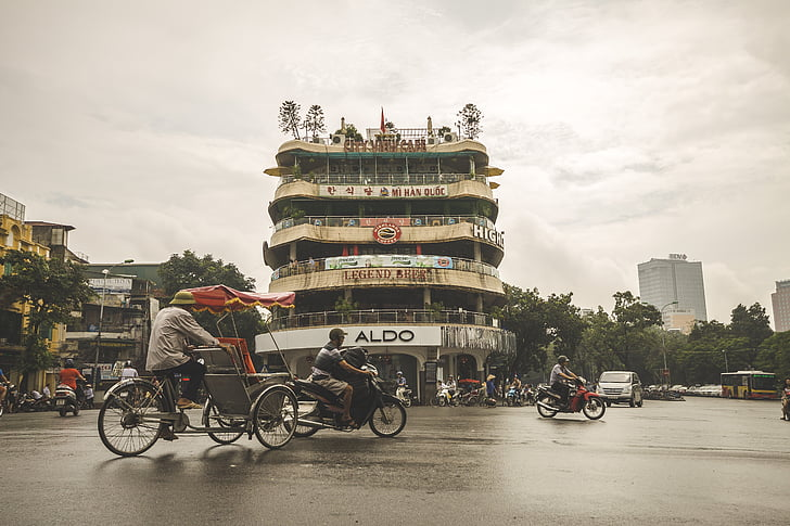 man riding trike near building