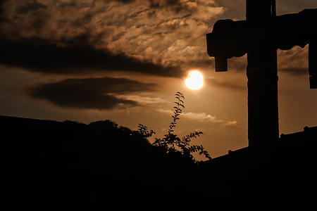 silhouette of cross on top of roof
