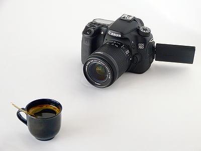black ceramic coffee cup on white surface near black Canon EOS DSLR camera