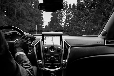 grayscale photo of man driving car