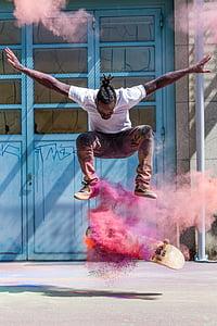 man wearing white shirt skateboarding with pink powder effects