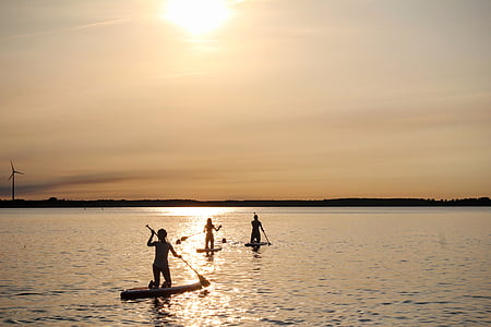 three people riding paddle board under golden hour