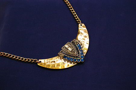 photo of blue gemstone encrusted gold-colored pendant