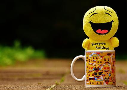 smiling emoji plush toy on emoji print mug