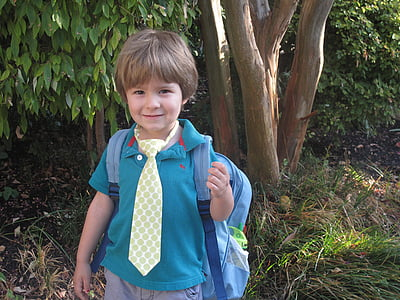 boy in blue polo shirt with backpack near tree