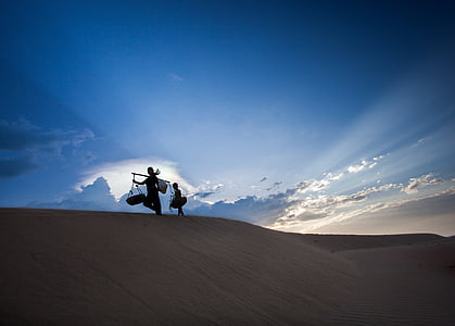 two people walking on top of sand dune under clear sky during daytime