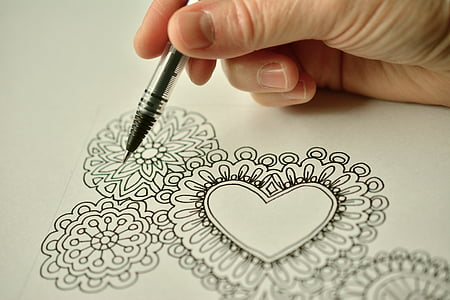 person holding pen drawing flowers
