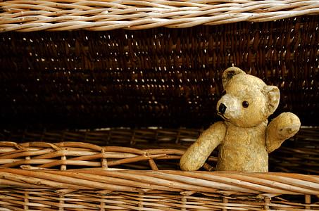 beige bear plush toy on brown wicker basket