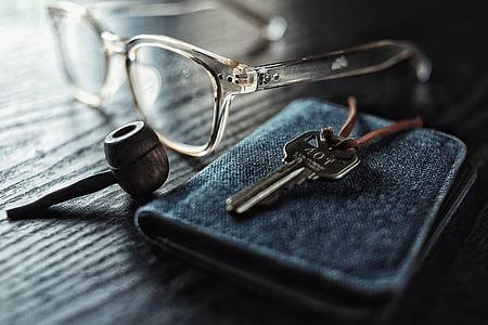 eyeglasses beside gray steel key