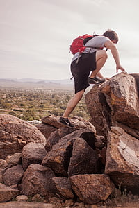 man climbing rock formation