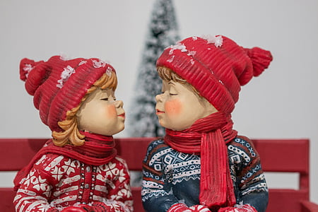 boy and girl wearing hat facing each other figurine