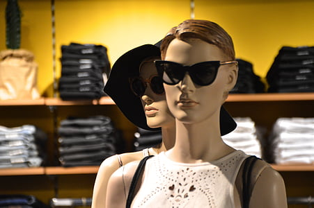 two woman mannequin wearing white sleeveless shirt in room