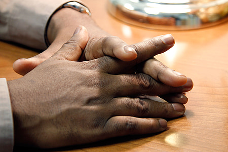 person's hand on brown wooden table