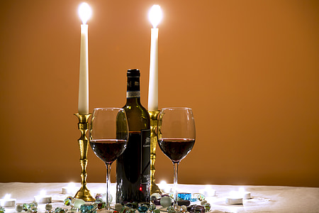 closeup photography of 3/4 full wine bottle in the middle of tall candlestick and wine glasses