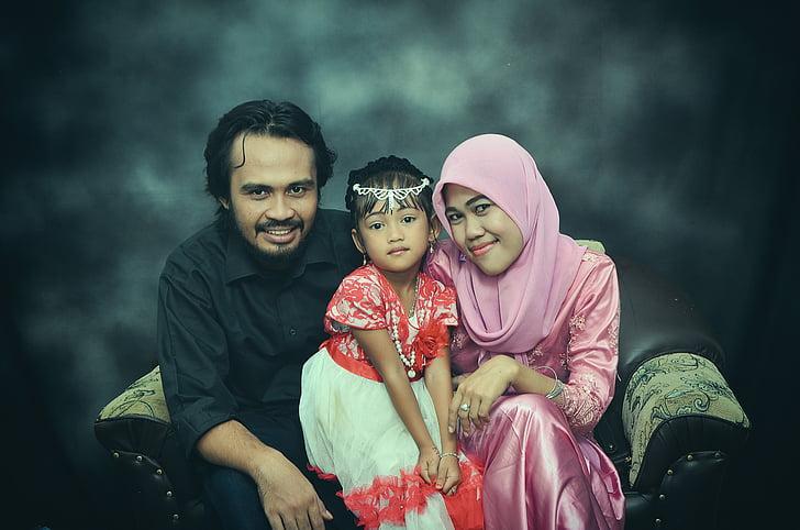 man sitting beside girl wearing red dress and woman wearing pink hijab