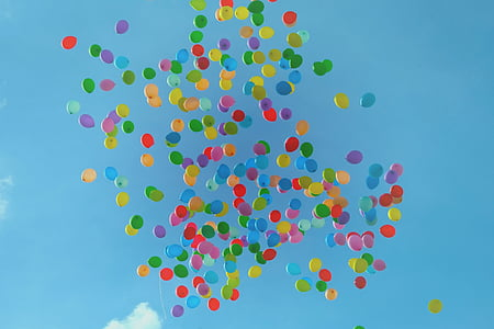 assorted-colored inflated latex balloons floating under blue sky