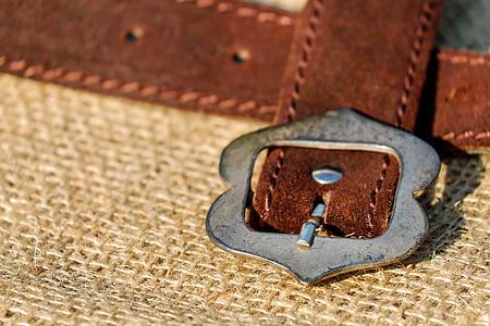 brown leather belt with silver-colored buckle