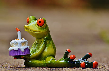 frog holding cake figurine