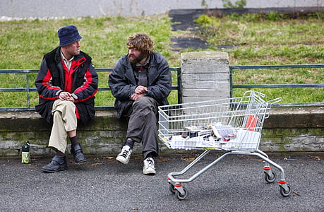 two men sitting on bench near white shopping cart
