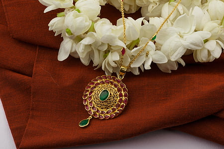 round gold-colored medallion pendant on top of brown fabric sheet