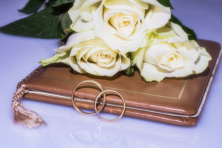 two gold-colored couple ring on book with bouquet